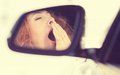 Sleepy tired fatigued yawning exhausted woman driving her car side view mirror view reflection young in traffic after long hour Stock Images