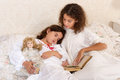 Sleepy victorian girl vintage in bed reading a bedtime story to her little sister Stock Photo