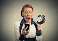 Sleepy woman with mobile phone and alarm clock Royalty Free Stock Photo