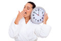 Sleepy woman yawning with a clock over white background Stock Image