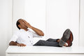 Sleepy young successful african businessman yawning, sitting at workplace. Royalty Free Stock Photo