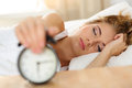 Sleepy young woman trying kill alarm clock Royalty Free Stock Photo