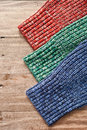 Sleeves of three colorful wool jumpers on a wood surface Royalty Free Stock Photos