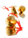 Sleigh bell with red ribbon shiny golden satin tie on reflective surface selective focus bells in background out of Royalty Free Stock Images