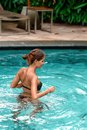 Slender tanned woman swimming at the pool. Rest and spa. Close up