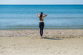 A slender woman walks to the sea after a run Royalty Free Stock Photo