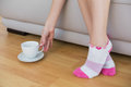 Slender woman wearing pink socks reaching for a cup sitting on couch Royalty Free Stock Photo