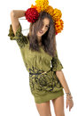 Slender young cheerful girl brown hair dances with a bouquet of colorful flowers on her head Royalty Free Stock Photo