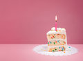 Slice of Birthday Cake with Candle on Pink Royalty Free Stock Photo