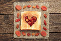 Slice of bread and dried fruit with cut out heart shape on wooden table Royalty Free Stock Photography