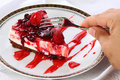 Slice of cheesecake on plate cut with sweet fork strawberries and mixed berries served decorated white by man hand a Royalty Free Stock Photos