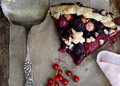Slice of fruit pie large a with a variety and berries on a napkin with spoon nearby Stock Photo