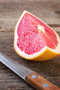 Slice of grapefruit and knife Royalty Free Stock Photo