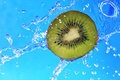 Slice of kiwi in the water with bubbles on blue background Stock Photography