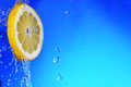 Slice of lemon in the water with bubbles on blue background Stock Photography