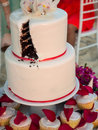 Slice missing from wedding cake white red and pink with a after the bride and groom have cut it with small cupcakes surrounding Royalty Free Stock Photography