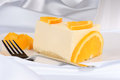 Slice of orange bavarian cream bavarese and a dessert fork on a white porcelain dish Stock Images