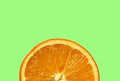 Slice of orange isolated on a green background Royalty Free Stock Images