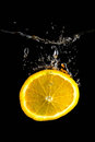 Slice of orange in the water on black Stock Photos