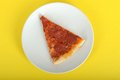 Slice of pepperoni pizza on a plate against a yellow background Royalty Free Stock Photo