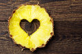 Slice pineapple with a cut in shape of hearts on vintage wooden background Stock Photo