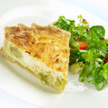 Slice of quiche made from leek and goats cheese on a plate with leafy salad Royalty Free Stock Photography