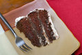 Slice of rich moist chocolate cake a with plate fork and red napkin Royalty Free Stock Image
