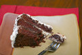 Slice of rich moist chocolate cake a with plate fork and red napkin Stock Photo