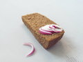 Slice of rye bread with red onion arranged on light wooden background. Royalty Free Stock Photo