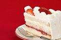 Slice of strawberry cream cake homemade against red background Stock Image