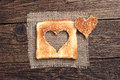Slice of toast bread with cut out heart shape on vintage wooden background Stock Images