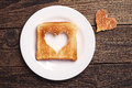 Slice of toast bread with cut out heart shape on wooden background Royalty Free Stock Photo