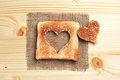Slice of toast bread with cut out heart shape on wooden table Stock Photography