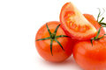 Slice of tomato on whole tomatoes lying on the right close-up isolated on white Royalty Free Stock Photo