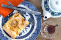 Slice of turkish borek served with a cup of tea delicious homemade on plate cutlery freshly brewed and teapot Royalty Free Stock Photography