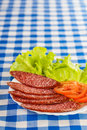 Sliced ​​smoked sausage tomatoes lettuce background tablecloth Royalty Free Stock Photo
