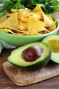 Sliced ​​avocado on a wooden board and tortilla corn chips in the background Royalty Free Stock Image