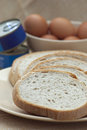 Sliced bread canned food and fresh eggs in a bowl Stock Photo