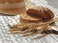 Sliced bread with wheat spikelets on wooden chopping board and blurred straw hat on background Royalty Free Stock Photo
