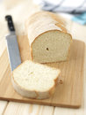 Sliced bread on a wooden table with tablecloth and knife Royalty Free Stock Photo