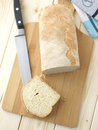 Sliced bread on a wooden table with tablecloth and knife Royalty Free Stock Photos