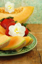 Sliced Cantaloupe, Strawberries, and Flowers. Stock Images