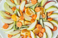 Sliced carrots, apple, kiwi, tangerine, and oranges, fruit theme Royalty Free Stock Photo