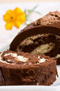 Sliced chocolate roll with a fresh flower Royalty Free Stock Photography
