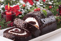 Sliced Christmas yule log cake on plate with candle Royalty Free Stock Photo