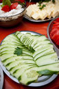 Sliced cucumbers on buffet dish of table with pieces of cheese in background Stock Photography