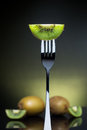 Sliced fresh and juicy green kiwi on the fork with whole kiwi in Royalty Free Stock Photo