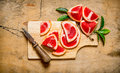Sliced grapefruit on a wooden Board with leaves. Royalty Free Stock Photo