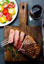 Sliced grilled medium rare beef steak served on wooden board Barbecue, bbq meat beef tenderloin. Top view, slate background Royalty Free Stock Photo