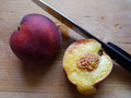 Sliced juicy peach the two peaches and the knife are positioned on a wooden plate Royalty Free Stock Photography